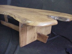 Slab table of solid White Oak. Live natural edged top. Sharp corner traditional legs.